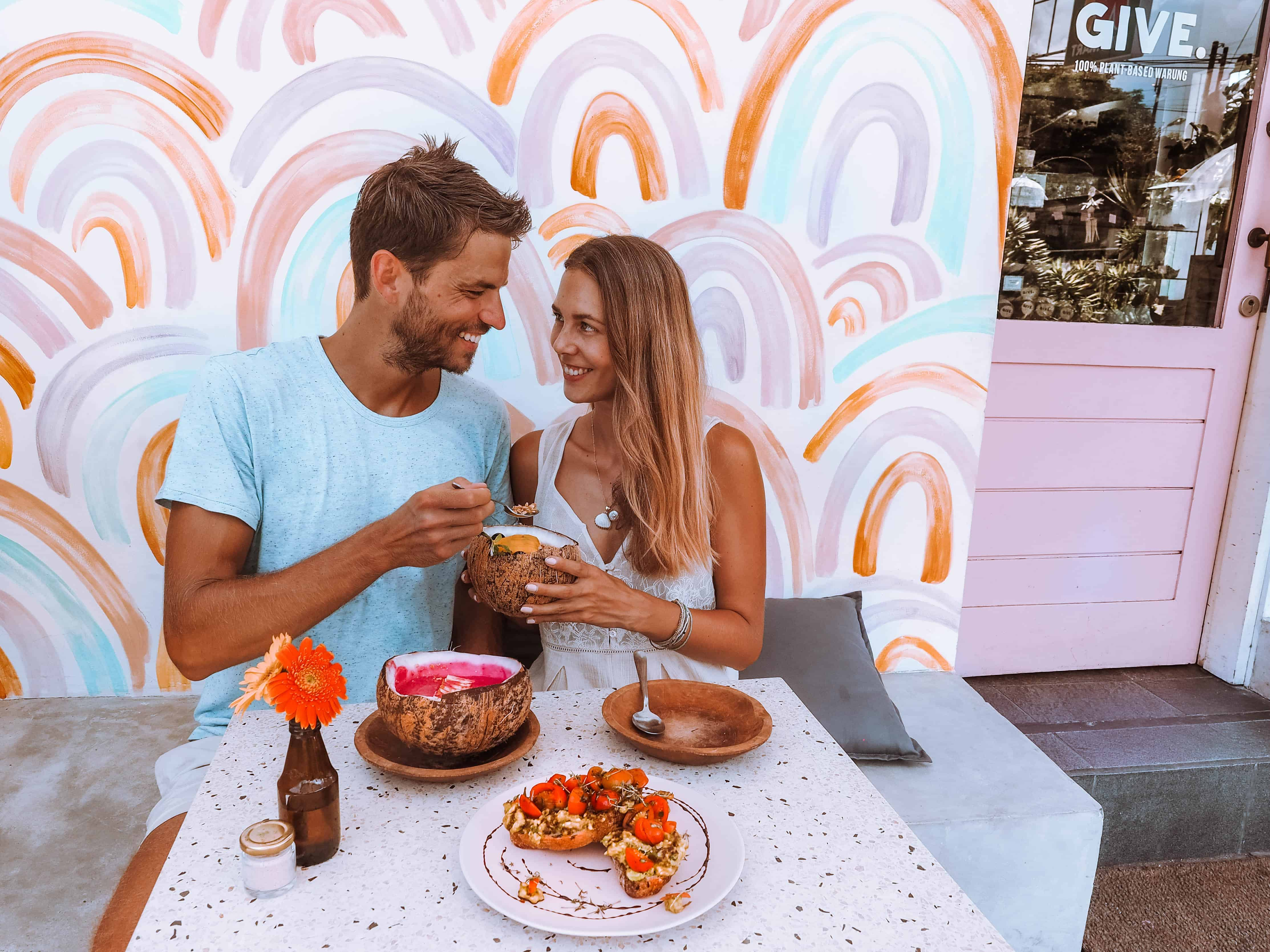 couple eating smoothie bowls at give cafe canggu bali