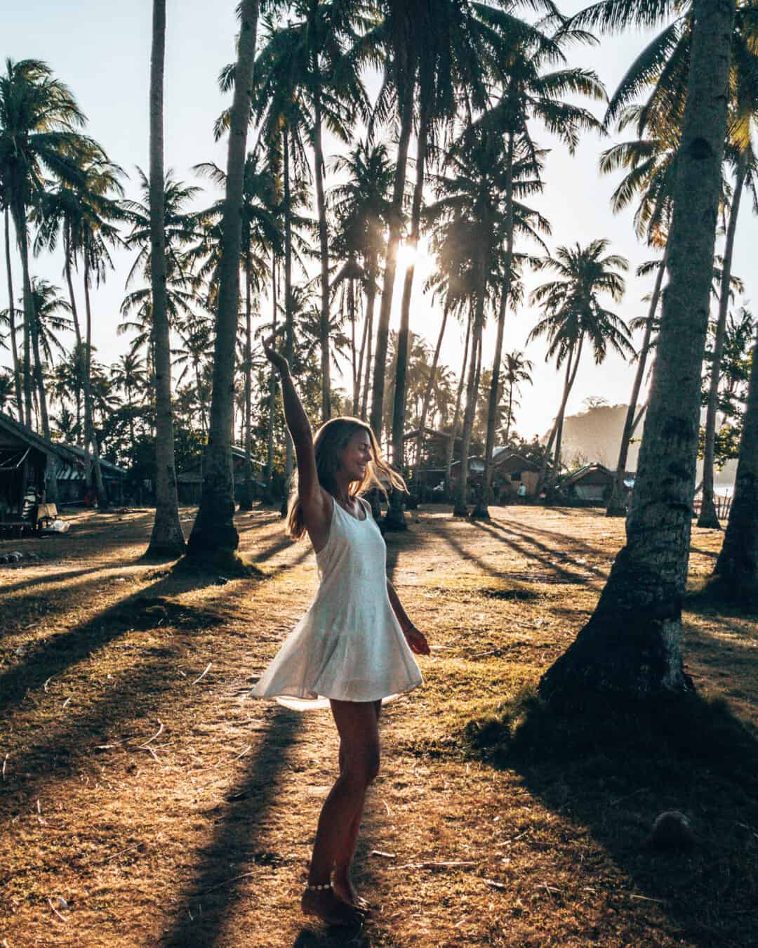 Women is dancing between palm trees at Nacpan Beach El Nido Philippines