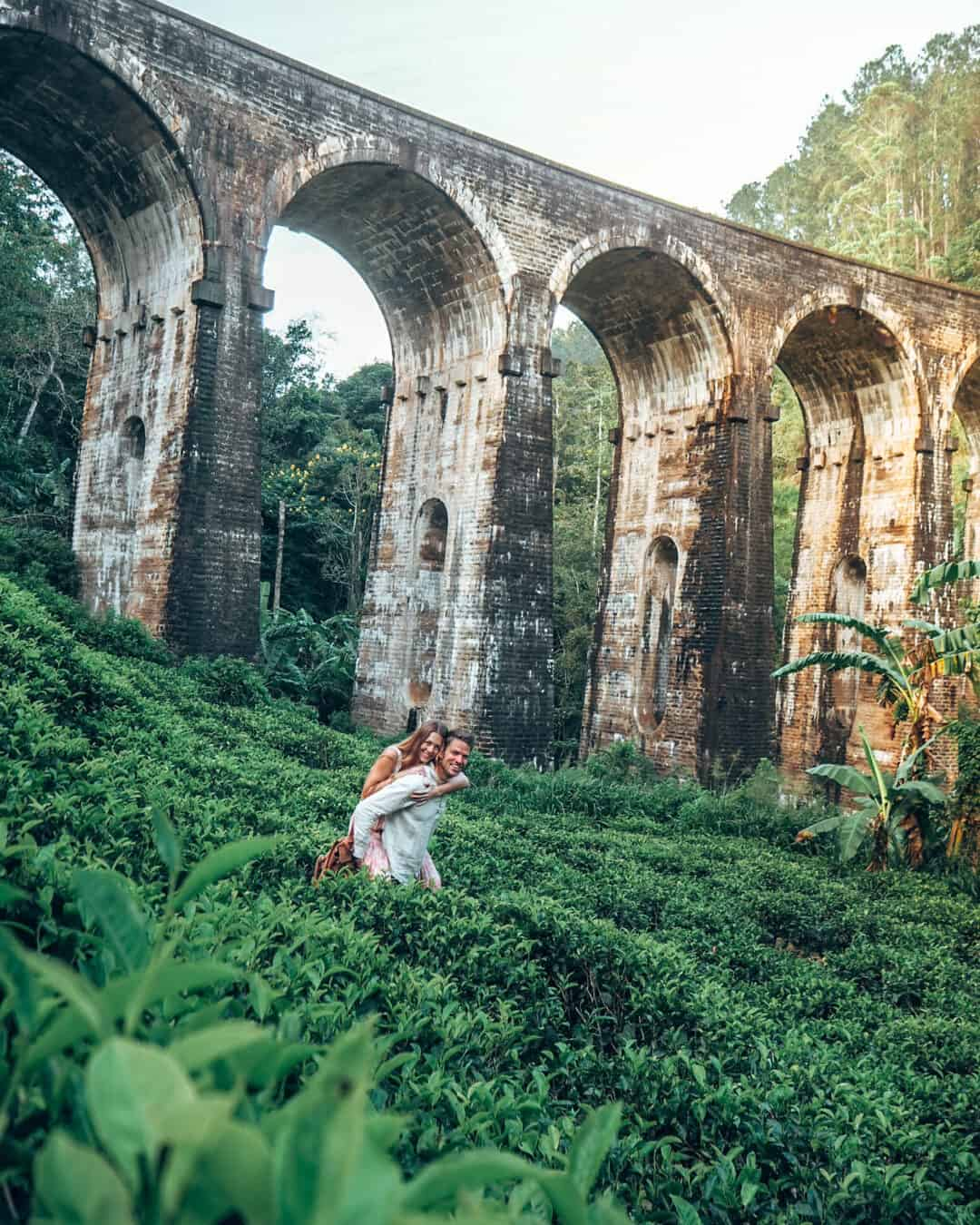 Couple in tea field in front of nine arches bridge ella