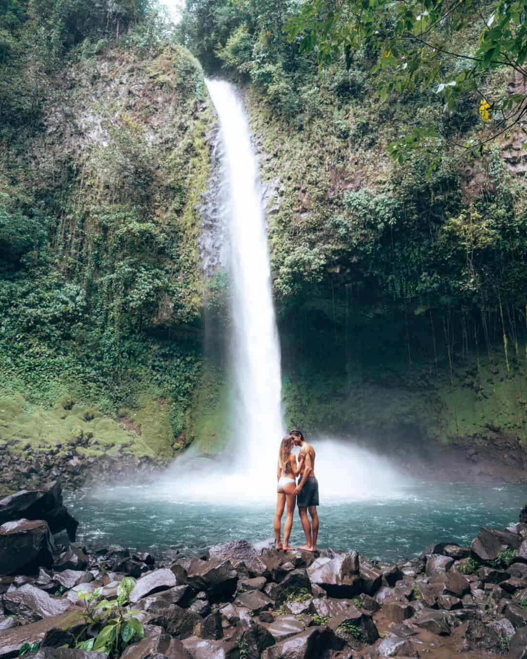 Couple standing in front of La Fortuna Waterfall Costa Rica