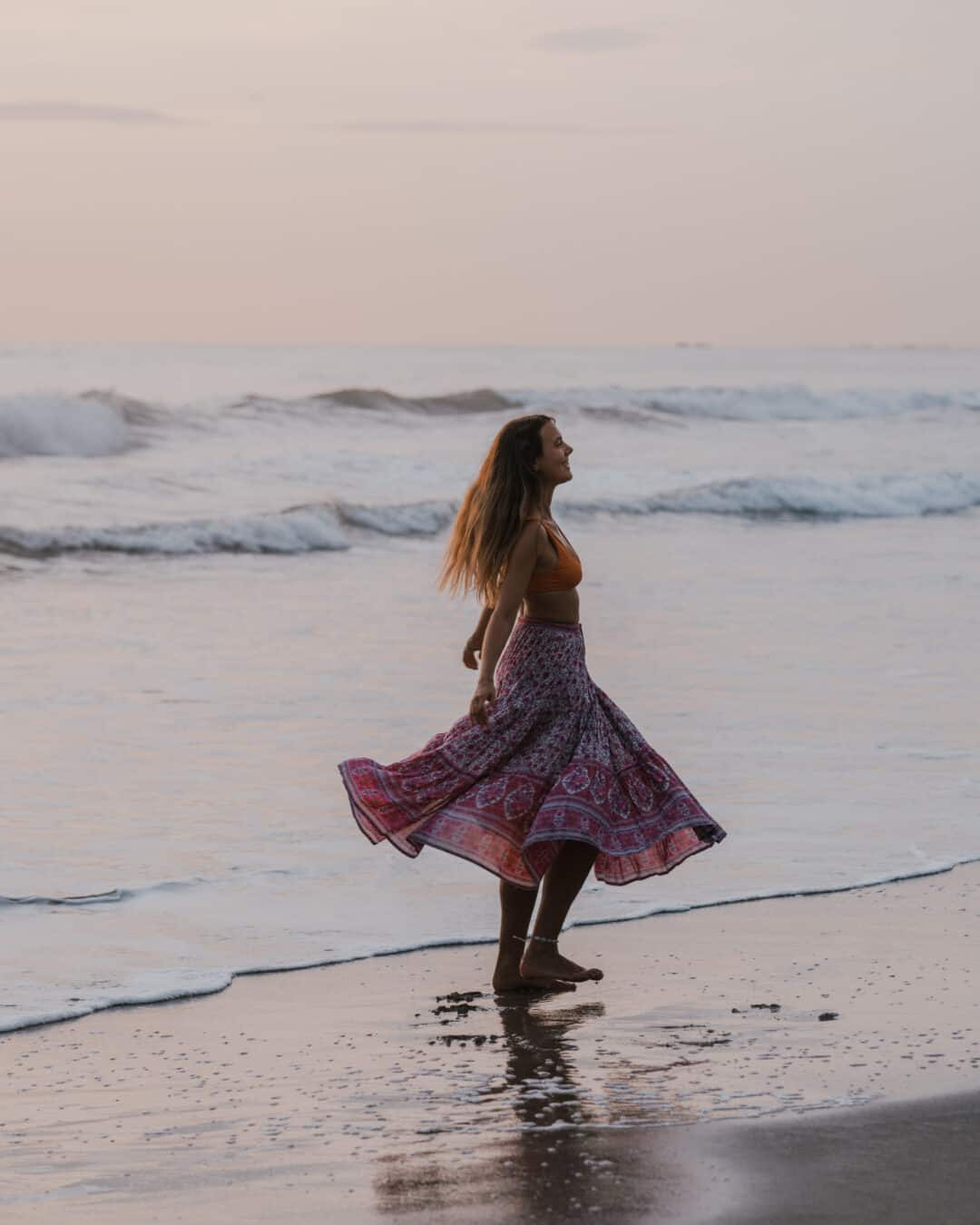 Woman dancing at the beach with sustainable clothing