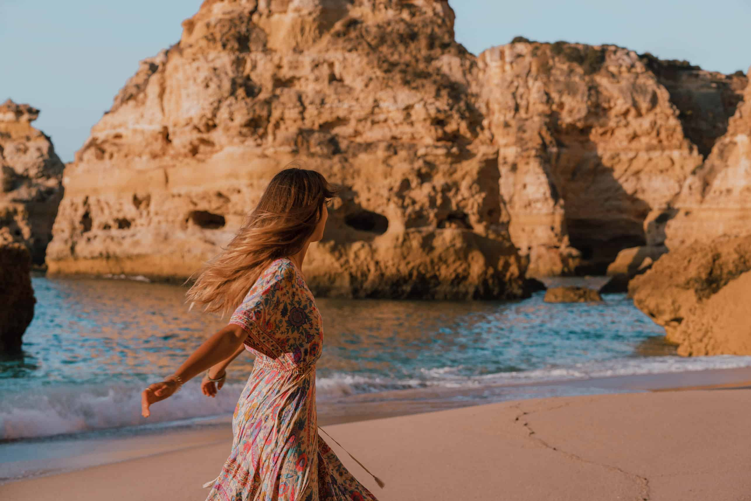 Girl in a dress dancing on the beach